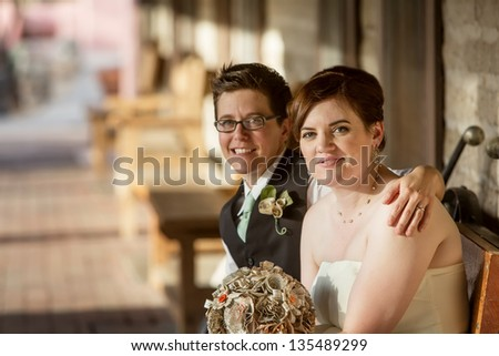 Cheerful Caucasian gay female couple sitting together