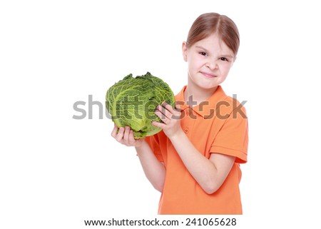 Cheerful caucasian little girl holding a head of cabbage/beautiful little with green cabbage (savoy) isolated over white background