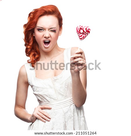 cheerful caucasian red-haired winking young woman holding lollipop. isolated on white - stock photo