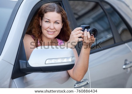 Cheerful Caucasian woman with digital camera sitting in her car and looking at cam