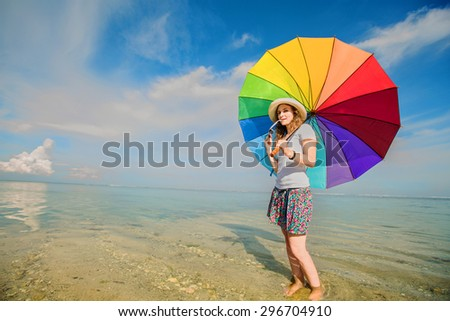 Cheerful caucasian young woman with rainbow umbrella having fun on the Jimbaran beach on Bali with beautiful ocean and blue sky on background - stock photo