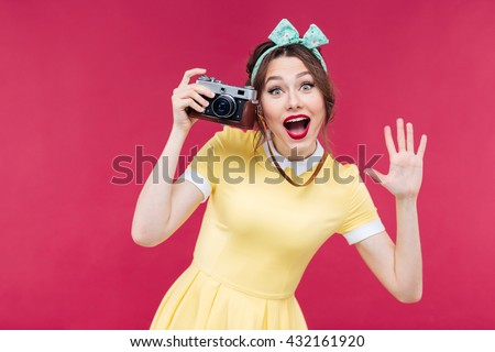 Cheerful charming pinup girl in yellow dress using vintage camera and taking pictures over pink background - stock photo