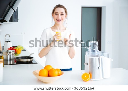 Cheerful charming young woman drinking juice and showing thumbs up at home - stock photo