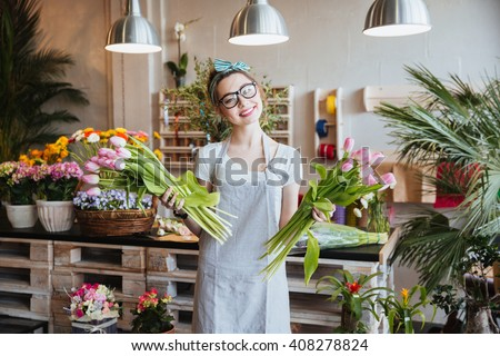 Cheerful charming young woman florist standing and holding two bunches of pink tulips in flower shop - stock photo