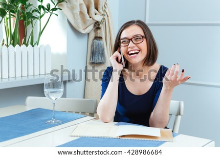 Cheerful charming young woman in glasses talking on mobile phone and laughing in cafe - stock photo