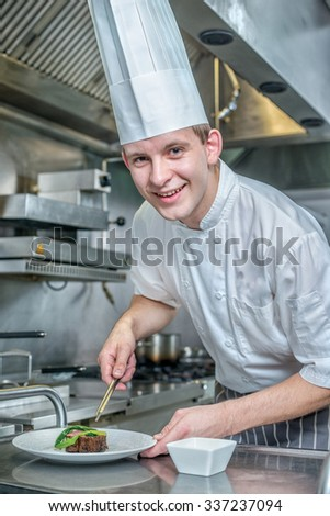 Cheerful Chef decorate plate with meat greens. Young chef preparing a delicious meal in the kitchen of the restaurant and looking at the camera - stock photo