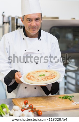 Cheerful chef presenting pizza in kitchen