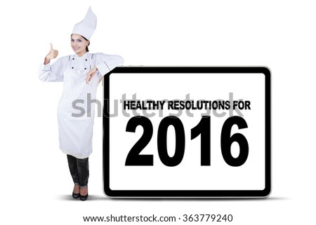 Cheerful chef woman showing ok sign and leans on the billboard with a text of healthy resolution for 2016 - stock photo