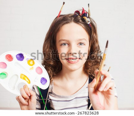 Cheerful child artist. Girl in classroom near easel - stock photo
