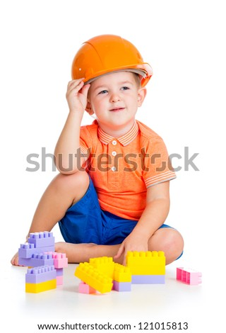 cheerful child boy with hard hat playing with building blocks toys over white background