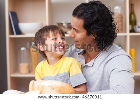 Cheerful child eating bread with his father in the kitchen