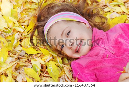 Cheerful child lying on leaves - stock photo
