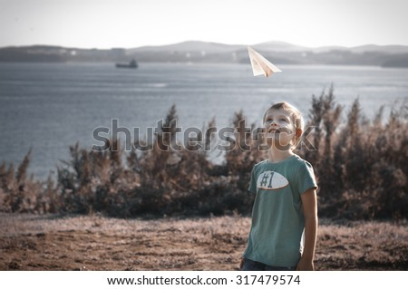 Cheerful child playing with paper airplane in the park - stock photo