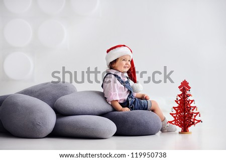 Cheerful child sitting on cushions. The girl laughs. Nearby is a red tree. White background. - stock photo
