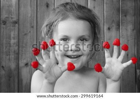 Cheerful child with a raspberries fingers. Food, fun, healthy food - stock photo