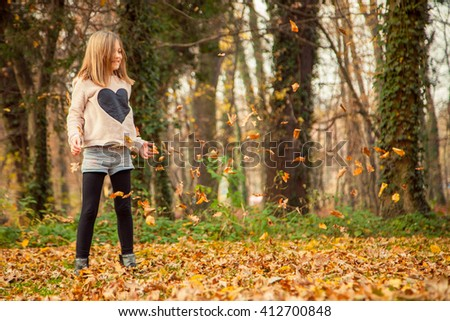 Cheerful child, with heart shaped shirt, plays with leaves in park on an autumn day. - stock photo