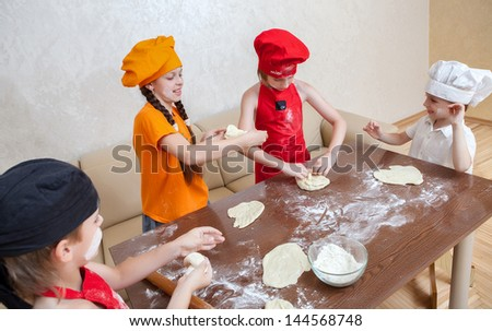 cheerful children cook pizza - stock photo