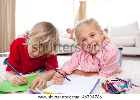 Cheerful children drawing lying on the floor in the living-room - stock photo
