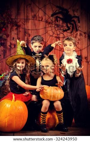 Cheerful children in halloween costumes celebrating halloween in a wooden barn with pumpkins. Halloween concept. - stock photo