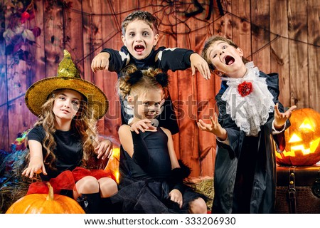 cheerful children in halloween costumes celebrating halloween in a wooden barn with pumpkins halloween concept - Halloween Barn