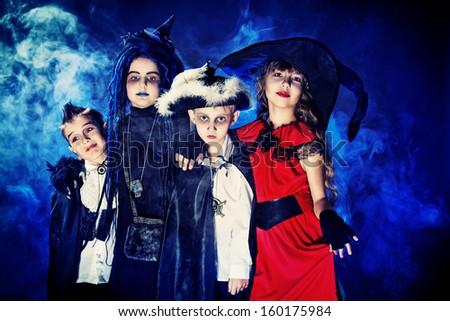 Cheerful children in halloween costumes posing over dark background. - stock photo