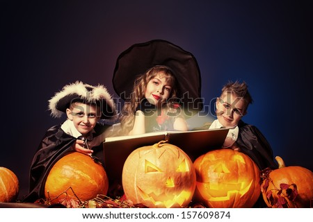 Cheerful children in halloween costumes standing with pumpkins and a book of spells. Over dark background. - stock photo