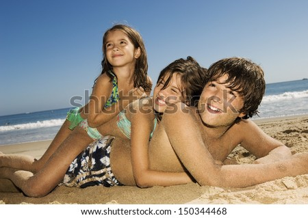 Cheerful children lying on top of each other while looking away at beach