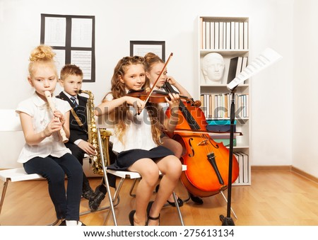 Cheerful children playing musical instruments - stock photo