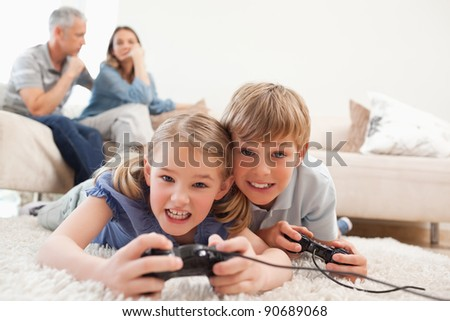 Cheerful children playing video games with their parents on the background in a living room - stock photo