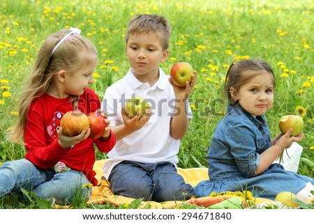 Cheerful children sitting among dandelions and eating apples - stock photo