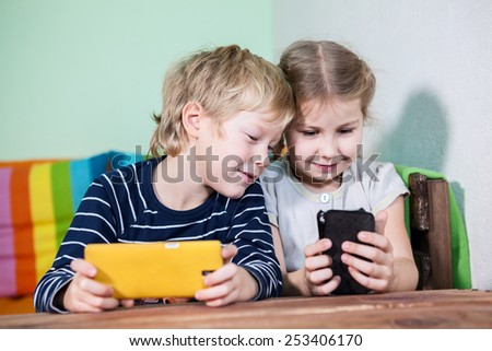 Cheerful children with smartphones in hands playing - stock photo