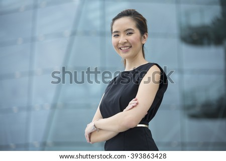 Cheerful Chinese business woman standing outside with office buildings in the background. Portrait of an Asian business woman looking at the camera. - stock photo