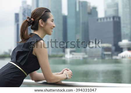 Cheerful Chinese business woman standing outside with office buildings in the background. Portrait of an Asian business woman looking away.