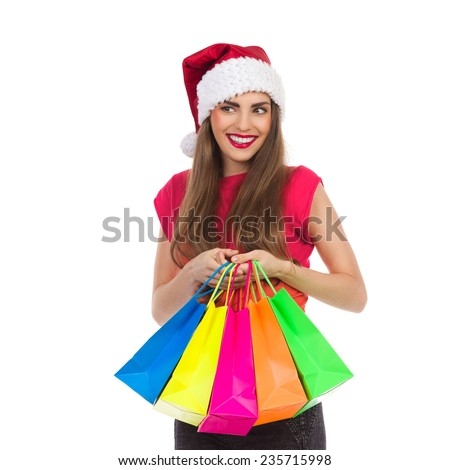 Cheerful christmas girl holding colorful shopping bags and looking away. Waist up studio shot isolated on white.