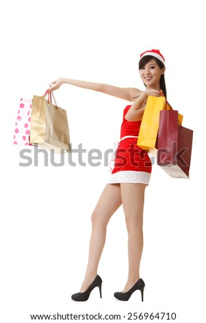 Cheerful Christmas lady holding shopping bags and smiling, full length portrait isolated on white background. - stock photo