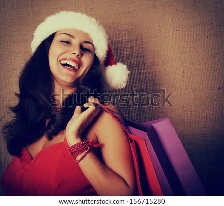 cheerful christmas woman in santa's hat smiling and holding shopping bags over canvas background, toned - stock photo