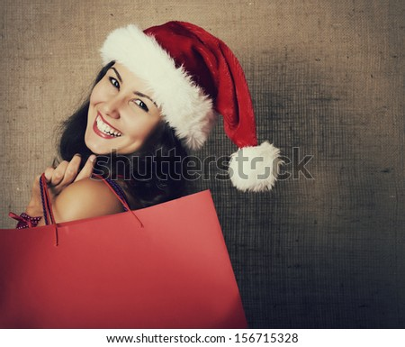cheerful christmas woman in santa's hat smiling and holding shopping bags over canvas background - stock photo