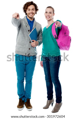 Cheerful classmates pointing finger to camera - stock photo