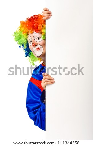 Cheerful clown peeking from blank white board. Isolated