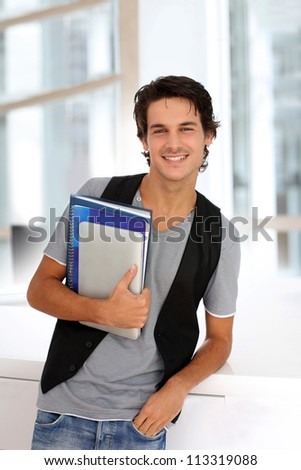 Cheerful college student standing in hall - stock photo