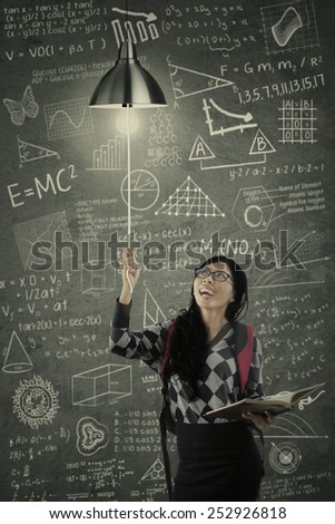 Cheerful college student switch on a light bulb in the class with a scribble background on the blackboard - stock photo