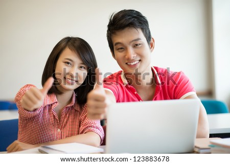 Cheerful college students expressing approval by showing thumbs up - stock photo