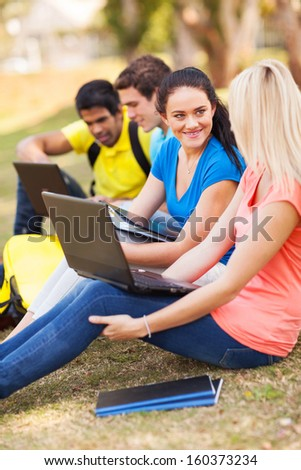 cheerful college students relaxing outdoors on campus - stock photo