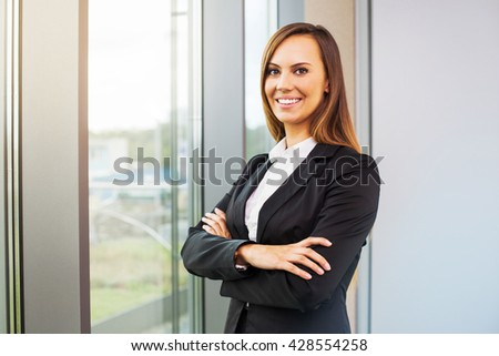 cheerful confident business woman standing in office near window - stock photo