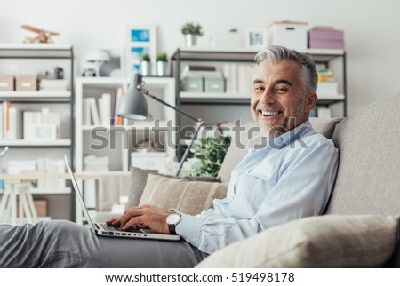 Cheerful confident businessman at home sitting on the couch and working with a laptop, he is smiling at camera