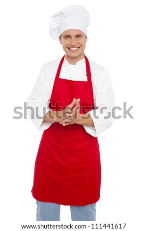 Cheerful confident male chef in proper uniform standing with hands together