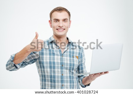 Cheerful confident young man holding laptop and showing thumbs up over white background  - stock photo