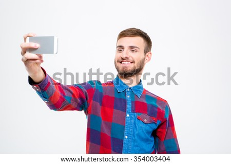 Cheerful confident young man in checkered shirt taking selfie using mobile phone