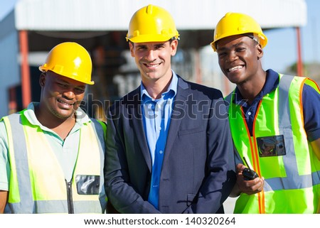 cheerful construction businessman and workers outdoors - stock photo
