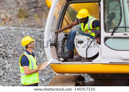 cheerful construction foreman talking to excavator operator - stock photo